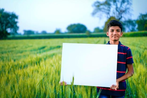 Młody indyjski dziecko z pustym plakatem przy indyjskim pszenicznym polem
