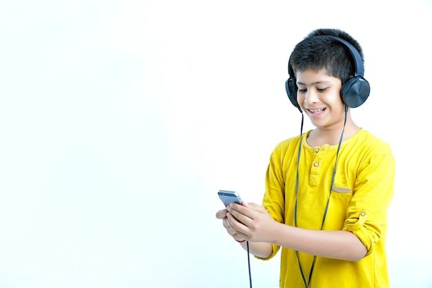 Młody indyjski ładny chłopiec słuchania muzyki w słuchawkach