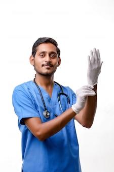 Młody indyjski lekarz zakłada rękawiczki ochronne na białym tle.