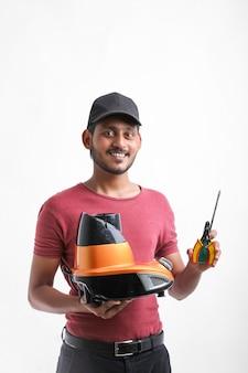 Młody indyjski mężczyzna, który naprawia sprzęt elektroniczny, trzymając w ręku narzędzia i mikser