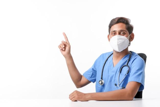 Młody indyjski mężczyzna lekarz noszenie maski i wskazując ręką w klinice.
