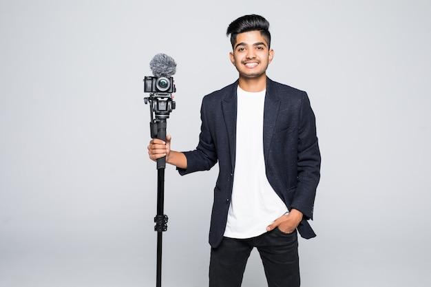 Młody indyjski mężczyzna operator kamery wideo na białym tle.