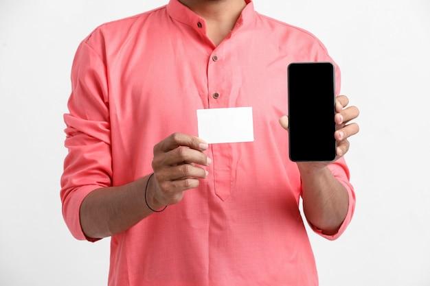 Młody indyjski mężczyzna pokazuje kartę i smartfon na białej ścianie