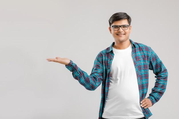 Młody indyjski mężczyzna pokazuje kierunek z ręką