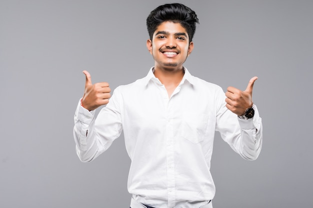 Młody indyjski mężczyzna stoi nad odosobnioną szarości ścianą zatwierdza robić pozytywnemu gestowi z ręką, aprobatami uśmiechniętymi i szczęśliwymi dla sukcesu