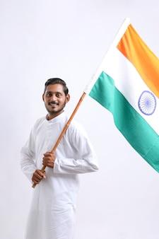 Młody indyjski mężczyzna trzymający w ręku indyjską flagę narodową na białym tle