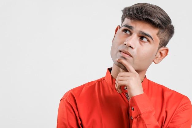 Młody indyjski mężczyzna w czerwonej koszula i myślącym dużym pomysle na bielu