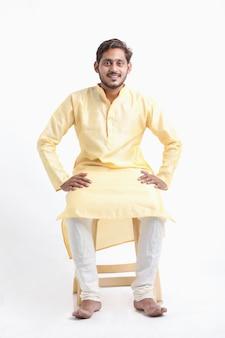 Młody indyjski mężczyzna w tradycji noszenia i siedzi na białej ścianie