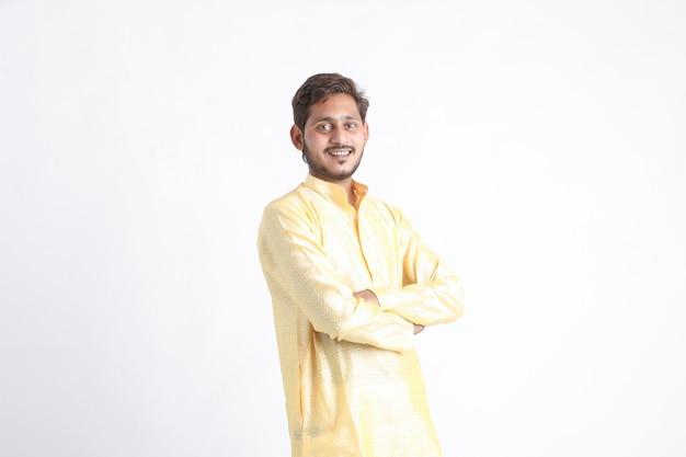 Młody indyjski mężczyzna w tradycji noszenia i stojąc na białej ścianie