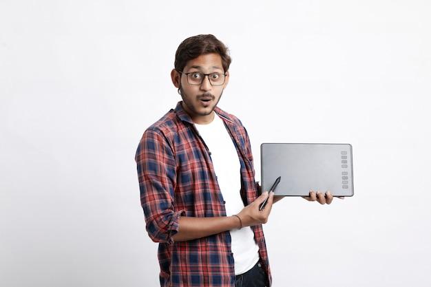 Młody indyjski profesjonalny projektant pokazujący tablet graficzny z piórem cyfrowym
