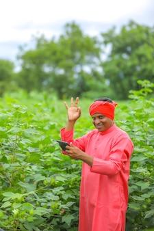 Młody indyjski rolnik korzystający z telefonu komórkowego do połączeń wideo