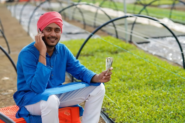 Młody indyjski rolnik liczący i pokazujący pieniądze w szklarni lub poli house