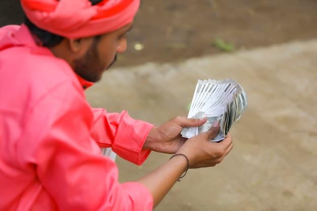 Młody indyjski rolnik liczący pieniądze