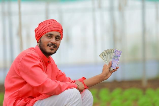 Młody indyjski rolnik liczy i pokazuje pieniądze w szklarni lub polyhouse