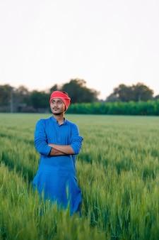 Młody indyjski rolnik na zielonym polu pszenicy