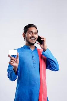 Młody indyjski rolnik pokazujący kartę i rozmawiający przez telefon komórkowy na białym tle