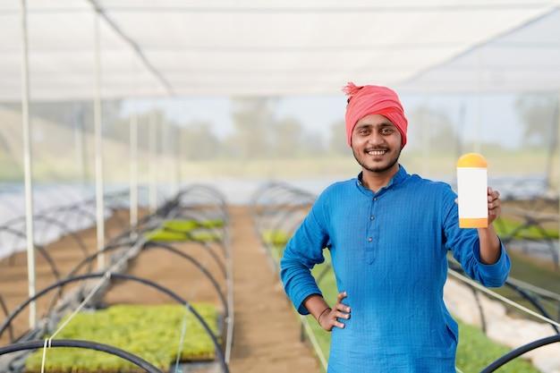 Młody indyjski rolnik pokazuje butelkę nawozu w szklarni