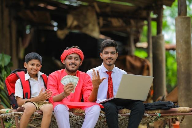 Młody indyjski rolnik pokazuje pieniądze z agronomem lub bankierem w domu