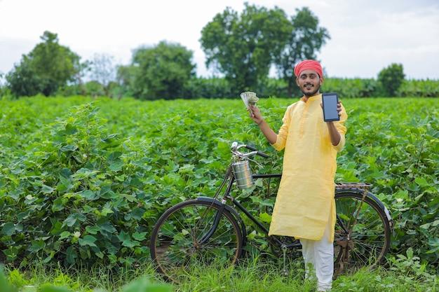 Młody indyjski rolnik pokazuje smartfon i pieniądze w polu bawełny