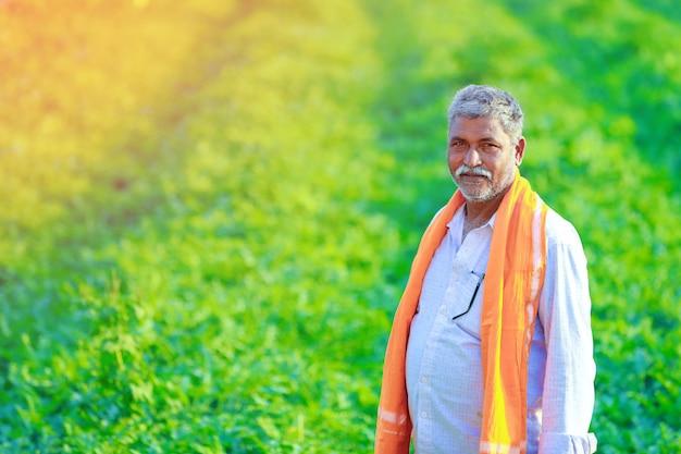 Młody indyjski rolnik przy polem.