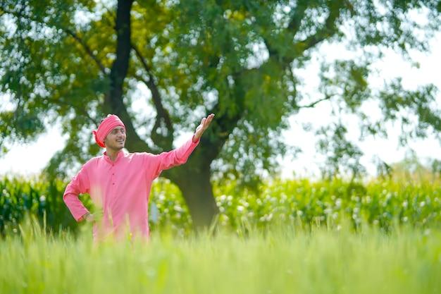 Młody indyjski rolnik stojący jego pole pszenicy i dając szczęśliwy wyraz