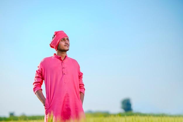 Młody indyjski rolnik stojący na zielonym polu pszenicy na tle nieba
