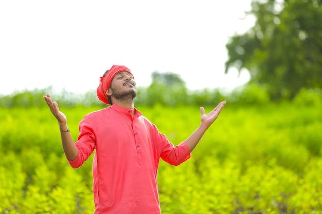 Młody indyjski rolnik stojący w polu zielony groch gołębi