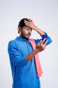 Młody indyjski rolnik szokujący i odczuwający stres po sprawdzeniu w smartfonie na białym tle.