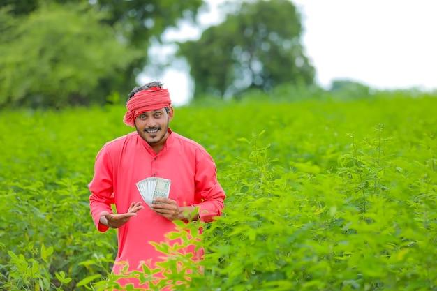 Młody indyjski rolnik z pieniędzmi na polu