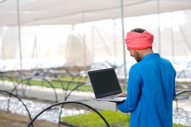 Młody indyjski rolnik za pomocą laptopa w szklarni lub domu poli