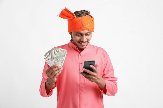 Młody indyjski rolnik za pomocą smartfona i pokazuje pieniądze na białym tle.