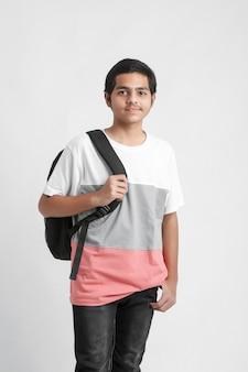 Młody indyjski student trzymając tornister na białej ścianie