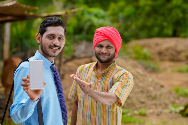 Młody indyjski urzędnik bankowy lub agronom pokazujący smartfona z rolnikiem na jego farmie