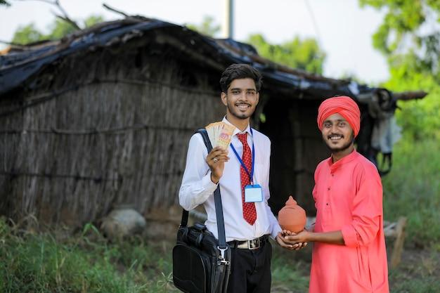 Młody indyjski urzędnik bankowy odwiedza biednego rolnika w domu