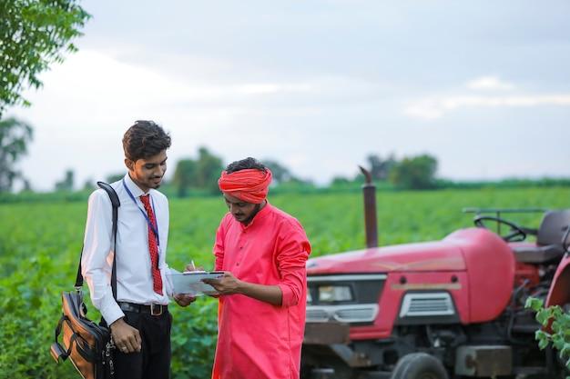 Młody indyjski urzędnik bankowy pokazujący szczegóły pożyczki dla rolnika w polu