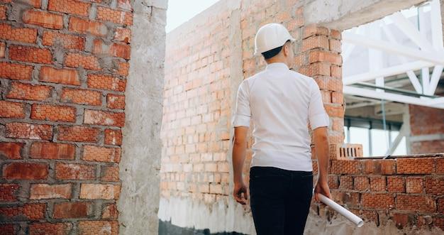 Młody inspektor weryfikujący zlecenie trzymając mapę i rozglądając się