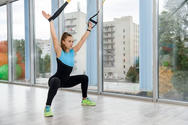 Młody instruktor brunetka ćwiczy z trx w studio aerobiku. trening funkcjonalny. sportowy styl życia