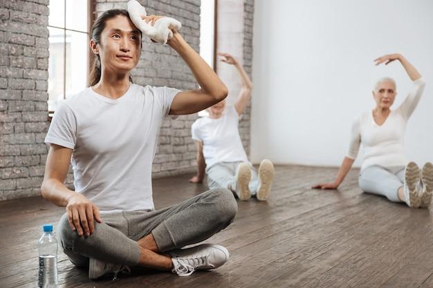 Młody instruktor długowłosy ubrany w białą koszulkę, trzymając wyprostowane plecy i krzyżując obie nogi