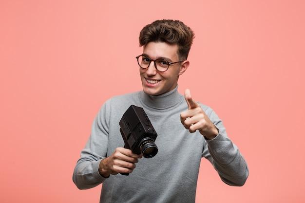 Młody intelektualista trzyma kamerę filmową wesoły uśmiecha się do przodu.
