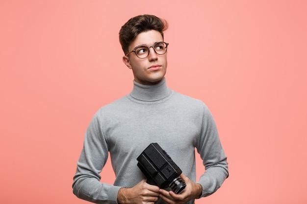 Młody intelektualista trzyma kamery filmowej uśmiecha się pewnie ze skrzyżowanymi rękami.