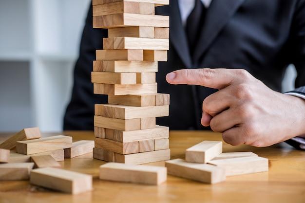 Młody inteligentny biznesmen bawić się drewnianą grę, ręki wykonawczy umieszcza drewnianego blok