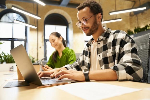 Młody inteligentny facet w okularach pracuje na laptopie, siedząc przy biurku ze swoją kobietą