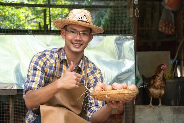 Młody inteligentny farmer, ubrany w kraciastą koszulę z długim rękawem, brązowy fartuch, trzyma świeże jaja kurze do kosza