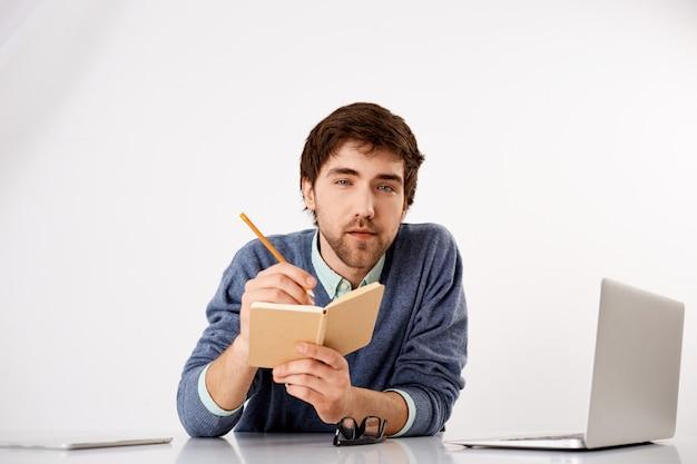 Młody inteligentny i zamyślony, przystojny facet spisujący porady i przydatne myśli, trzymający ołówek i notatnik, wyglądający na zainteresowanego