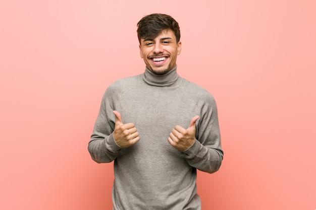 Młody inteligentny student człowiek podnoszący kciuki do góry, uśmiechnięty i pewny siebie.