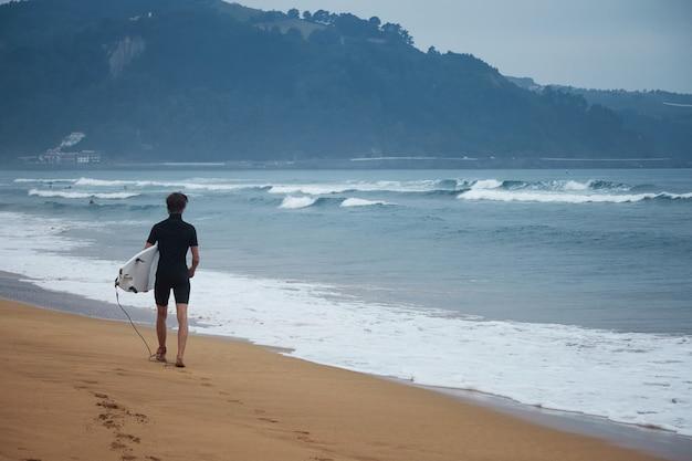 Młody internauta w piance spaceruje po plaży z białą deską surfingową, patrząc na fale
