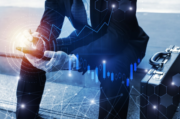 Młody inwestor lub biznesowy mężczyzna używa telefon komórkowego z graficznym globalnym sieci połączeniem