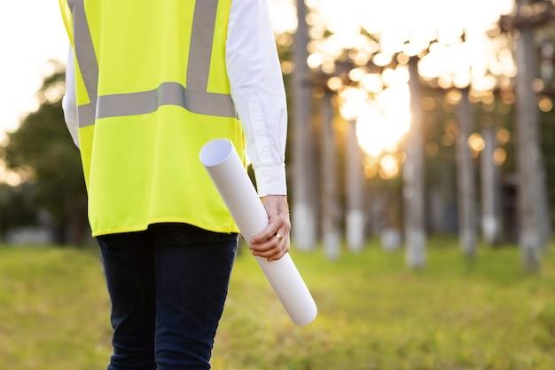 Młody inżynier architekt lub budowniczy trzymający w ręku projekt przed zasilaniem wysokiego napięcia