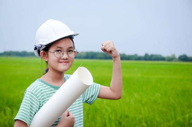 Młody inżynier azjatyckiej dziewczyny w białym kapeluszu bezpieczeństwa trzyma rolkę papieru.