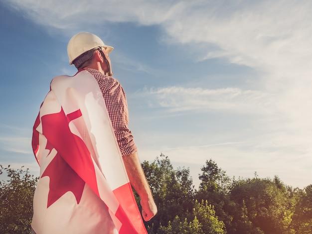 Młody inżynier, biały kask i flaga kanady